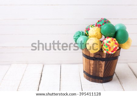 Cake pops in  decorative bucket  on white  painted wooden background. Selective focus. Place for text. - stock photo
