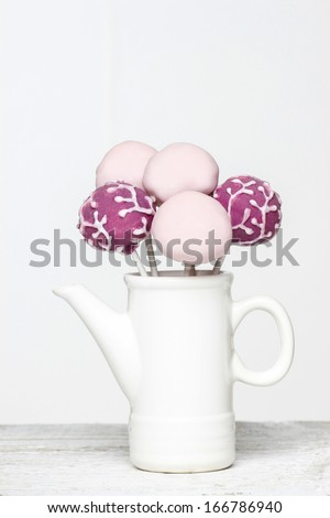Cake pops in white jug isolated on white background. Copy space - stock photo