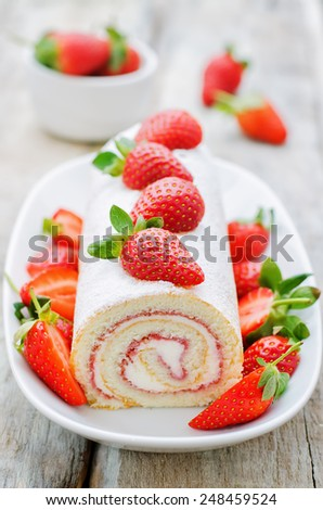 cake roll with strawberries and cream cheese on a white wood background. tinting. selective focus - stock photo