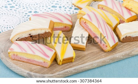 Cake Slices - Variety of colourful cake slices on a wooden board. - stock photo