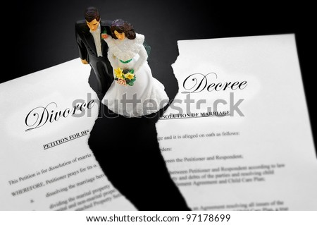 cake-topper wedding couple on a torn divorce document - stock photo