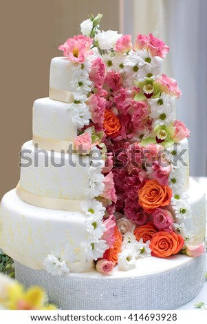 Cake traditional anniversary birthday wedding four-layer beautiful delicious sweet dessert decorated with butter-cream roses flowers on blurred background