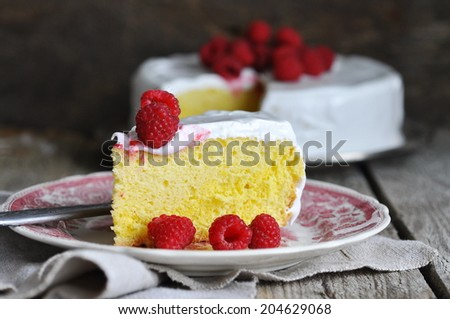 Cake tres leches with meringue frosting and raspberries, selective focus