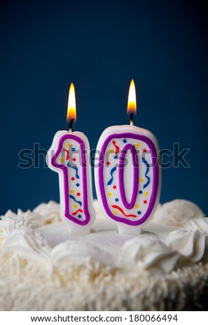 Cake: White Iced Birthday Cake With Candles For 10th Birthday - stock photo