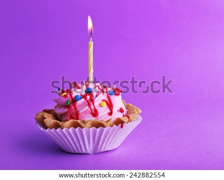 Cake with birthday candle on purple background - stock photo