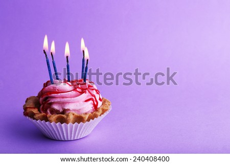 Cake with birthday candles on purple background - stock photo