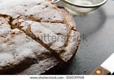 cake with black currants and sugar cut off piece on a wooden table - stock photo