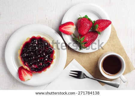 Cake with black currants, strawberry and coffee cup on table, top view - stock photo