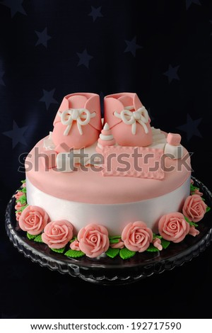 Cake with booties and toys made of marzipan - stock photo