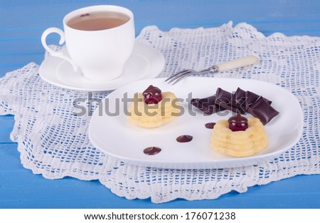 Cake with cherry, chocolate and cup of tea