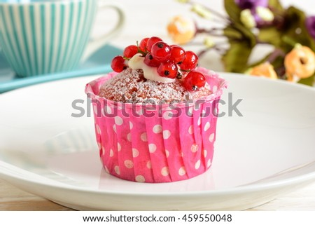 Cake with currants. Red cupcake on plate