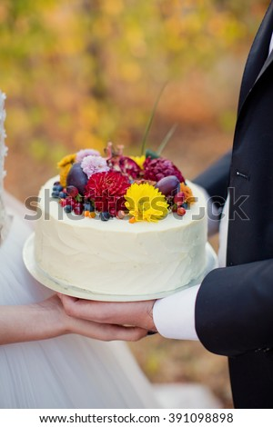 cake with flowers and fruits in the hands