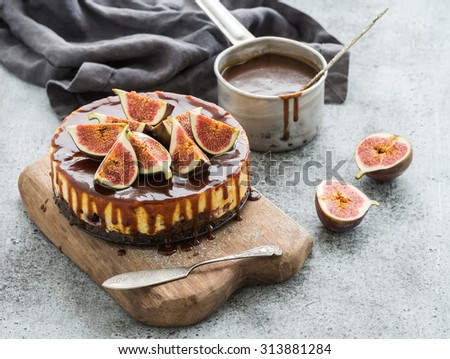 Cake with fresh figs and salted caramel on wooden serving board over grunge background, selective focus - stock photo