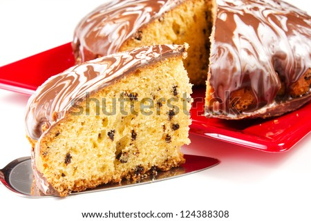 cake with glaze of chocolate in the red dish on the white table