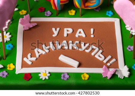 "Cake with mastic on prom night on black background. The names of students on the gingerbread. Chalk board of mastic with the inscription ""Cheers! Holidays!"". - stock photo"