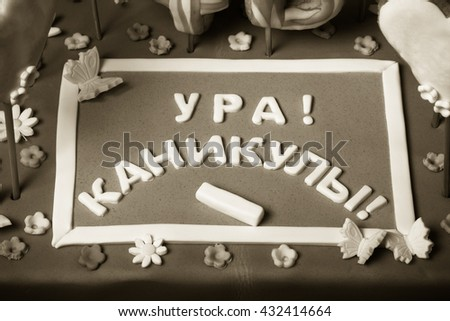 "Cake with mastic on prom night on black background. The names of students on the gingerbread. Chalk board of mastic with the inscription ""Cheers! Holidays!"". Toned. - stock photo"