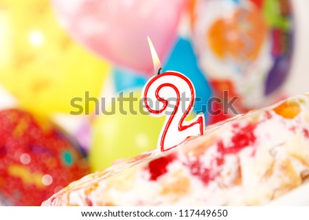 Cake with number 2 candle on balloons background.