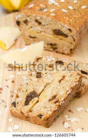 cake with oatmeal, quince and prunes on a wooden board - stock photo