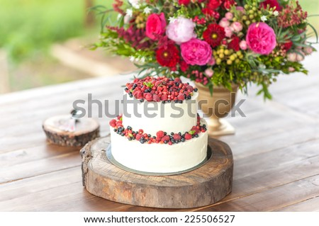 Cake with protein cream and fresh berries on a wooden cake stand outdoor