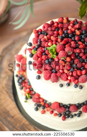 Cake with protein cream and fresh berries on a wooden cake stand outdoor - stock photo