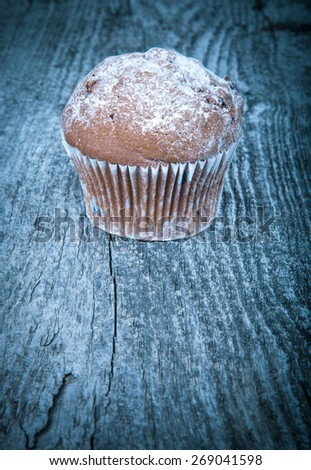 Cake with raisin and sugar powder on the wooden table. Toned. Selective focus. - stock photo