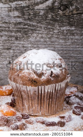 Cake with raisin, dry apricot and sugar powder on the wooden table. Selective focus. - stock photo