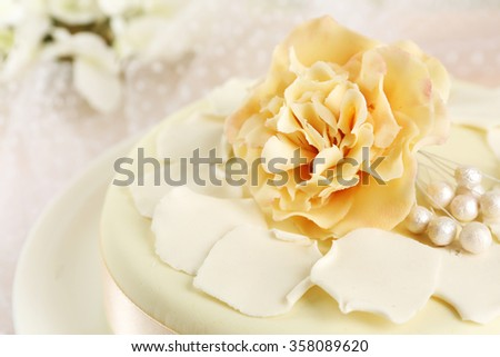 Cake with sugar paste flowers, on light background - stock photo