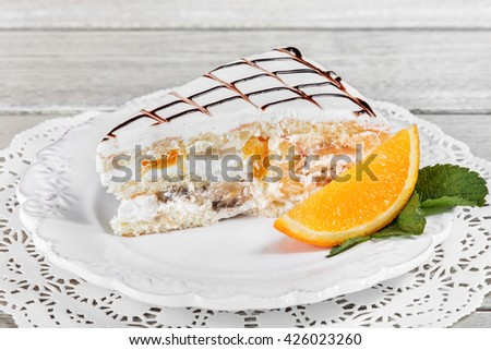 Cake with whipped cream, with banana and orange on plate, on a light wooden background. Selective focus - stock photo