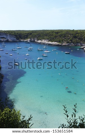 Cala in Menorca, Mediterranean sea. There are unknown people bathing, swimming or snorkeling. There are some sailboats, powerboats or yachts anchored