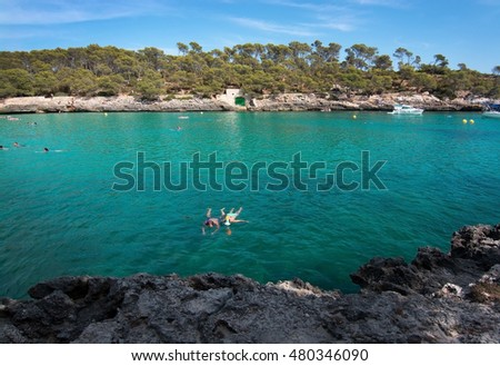 CALA MONDRAGO, MALLORCA, SPAIN - SEPTEMBER 4, 2016: Couple snorkeling in clear turquoise water on a sunny day on September 4, 2016 in Cala Mondrago, Mallorca, Spain.