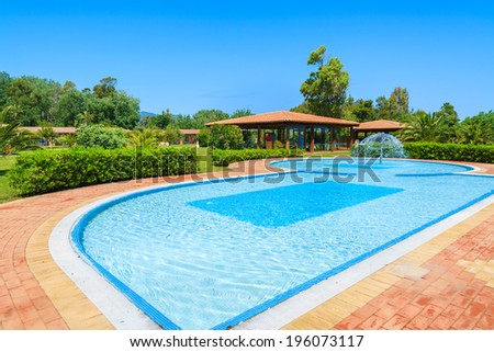 CALA SINZIAS, SARDINIA - MAY 24, 2014: swimming pool and tropical plants of luxury Garden Beach hotel, Sardinia island, Italy. Southern part of the island is popular for beach vacation among Europeans