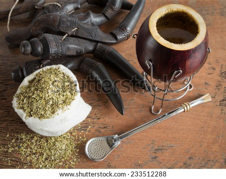 Calabash and bombilla with yerba mate on wooden background - stock photo