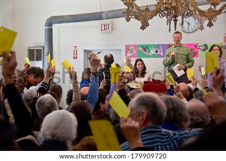 Calais, Vermont, USA - March 4, 2014: Voters raise yellow cards to register their vote on this vote from the floor at the Calais Town Hall during the school board meeting on Town Meeting Day. - stock photo