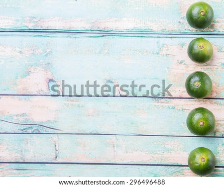 Calamansi citrus over weathered wooden background - stock photo