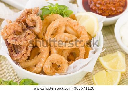 Calamari - Deep-fried squid rings served with garlic mayo and chili sauce.  - stock photo