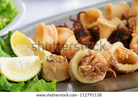 Calamari, deep fried squid with lettuce and lemon - stock photo
