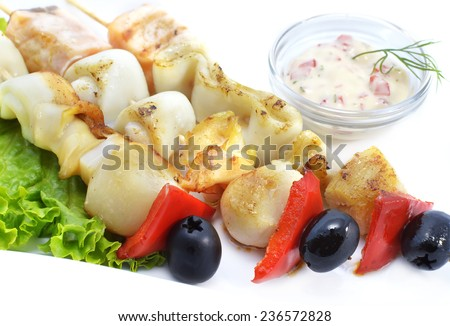 Calamari, fish and scallop with vegetables on wooden skewers, served with sauce, isolated on white, seafood grill, restaurant dish - stock photo