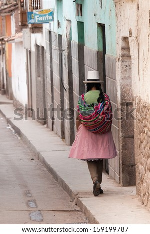 CALCA, PERU - CIRCA JAN 2010: Quechua woman walking the street of Calla, Peru in CIRCA JAN 2010. Calla is a town in the famous Sacred Valley of the Incas near in the Peruvian Andes.