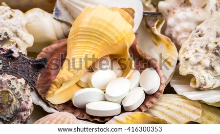 Calcium natural food supplement pills on the beautiful, mixed seashells background