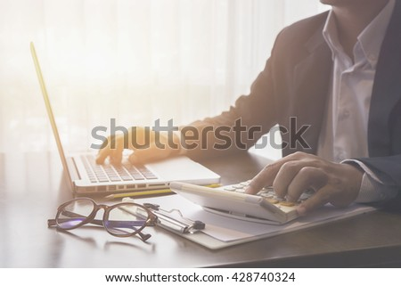 calculate,finance,accounting,Businessman analyzing investment charts with calculator .Accounting with technology,Business people using laptop at office,Analyze plans.selective focus,vintage color - stock photo