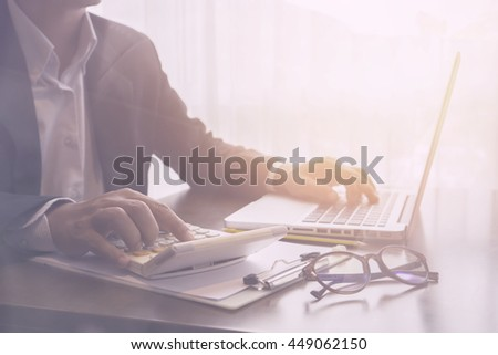 calculate,finance,accounting,Businessman analyzing investment charts with calculator .Accounting with technology,man using laptop at office Analyze plans.selective focus,vintage color - stock photo