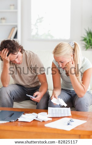 Calculating couple on a sofa in their living room - stock photo