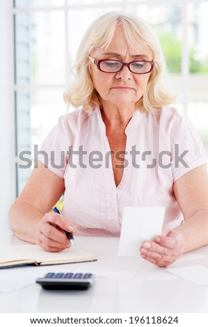 Calculating expenses. Concentrated senior woman holding a bill and writing something in her note pad while sitting at the table