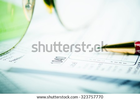 Calculating numbers for income tax return with pen - stock photo