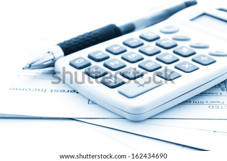 Calculating numbers for income tax return with pen and calculato - stock photo
