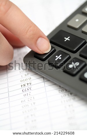 Calculating on a calculator. Financial statements. Closeup. - stock photo
