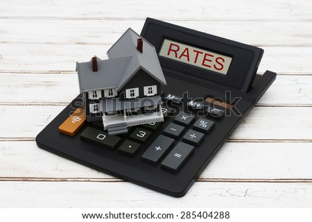 Calculating your  interest rates, A gray model house on a calculator with word Rates over a distressed wood background - stock photo