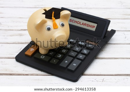 Calculating your scholarship, A golden piggy bank with a grad hat on a calculator with word Scholarship  over a distressed wood background - stock photo