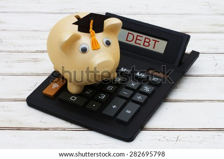 Calculating your student loan debt, A golden piggy bank with a grad hat on a calculator with word Debt over a distressed wood background - stock photo