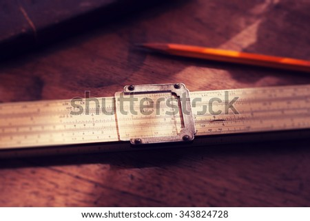 Calculation. Vintage calculating slide rule and pencil, on old desk. Intentionally shot in retro muted color. Shallow depth of field. - stock photo